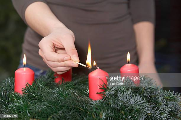 detail of woman lighting advent wreath