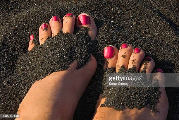 Detail of woman's feet with red painted toe nails in black volcanic sand.