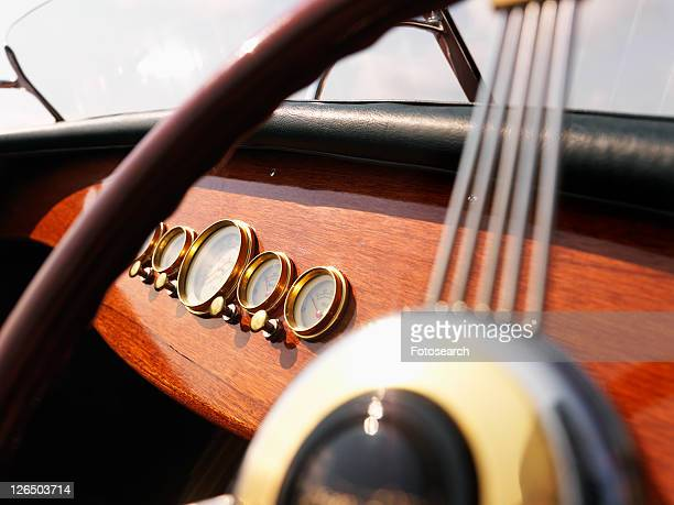 Detail of wooden boat with steering wheel and dashboard.