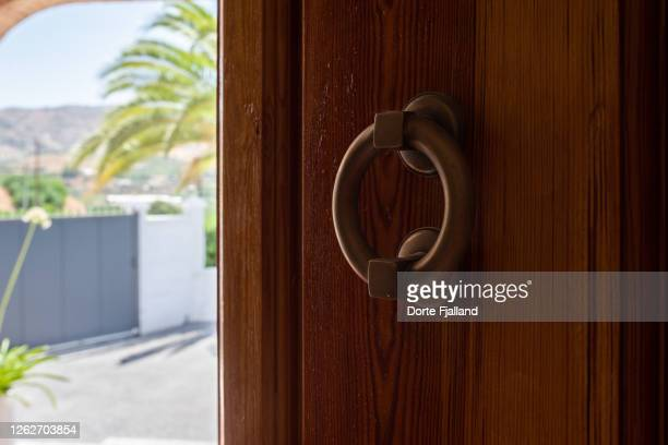 detail of wooden door with a brass knob opening to the bright outside - dorte fjalland fotografías e imágenes de stock