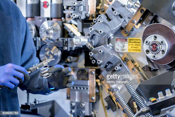detail of worker measuring spring in automotive parts factory - monty rakusen stock pictures, royalty-free photos & images