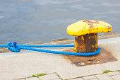 blue rope old yellow mooring bollard