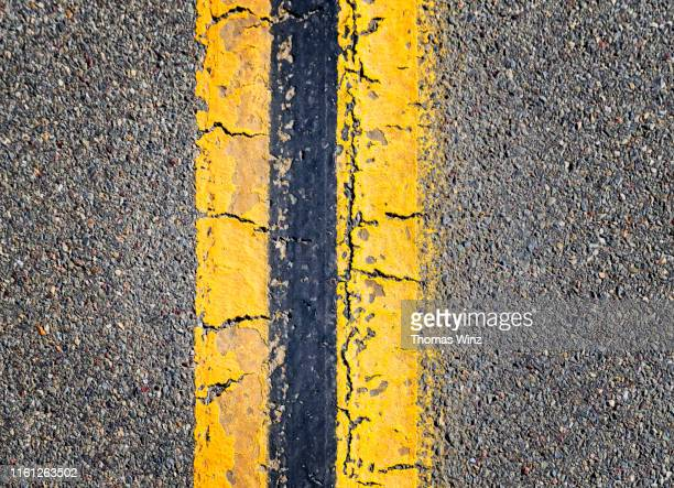 detail of yellow dividing line from above - dividing line road marking stock pictures, royalty-free photos & images
