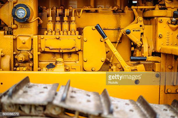 Detail of yellow gears, levers and valves of a tractor engine
