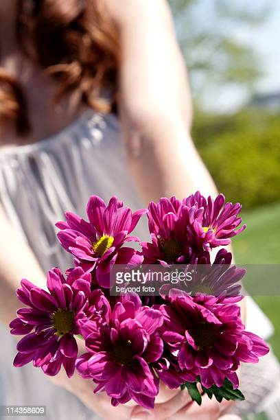 detail of youg woman holding bunch of purple flowers