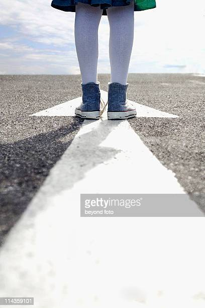 detail of young girl standing on arrow sign on road