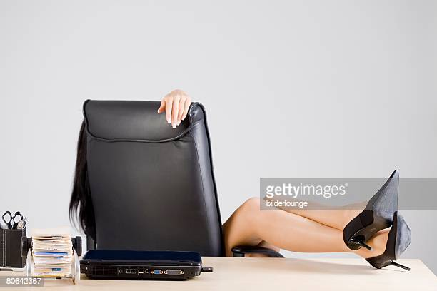 detail of young office worker putting her legs on the desk