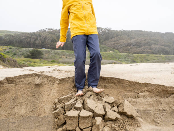 Detail of young person standing on crumbling edge of sandy ledge