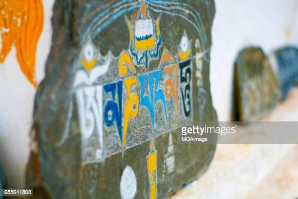 detail on a carved and painted mani (prayer) stone, (a stone carved with the tibetan buddhist chant) - mount everest deaths stock photos and pictures