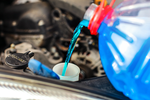 Detail on antifreeze car screen wash liquid pouring into dirty car from blue and red anti freeze water container. 998703506