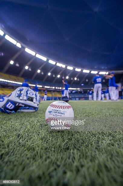 A detail shot of a baseball and glove on the field as members of the Toronto Blue Jays warm up prior to the exhibition game against the Cincinnati...