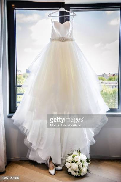 detail shot of a bride's wedding dress, shoes, and bouquet in front of a window in berlin, germany summertime - robe de mariée photos et images de collection
