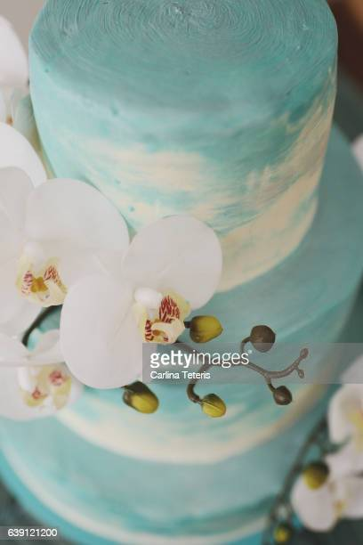 Detail shot of a turquoise ombre wedding cake with white orchids