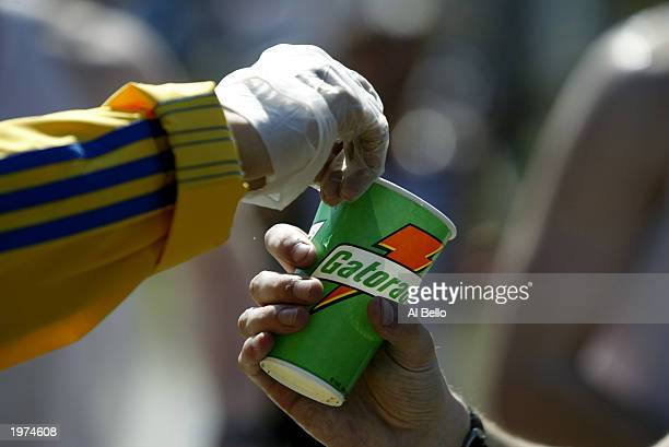 A detail shot of a volunteer as he hads a Gatorade refreshment cup to a runner as he passes through a water station in the town of Natick during the...