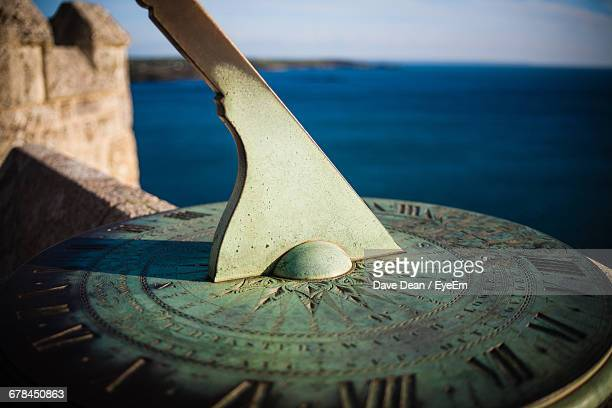Detail Shot Of Sundial Against Calm Sea