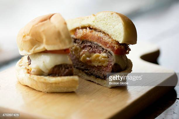 A detail shot of the hamburger stuffed with macaroni and cheese with a baked tomato and Panko crust on it sliced in half Dan Whalen author of Stuffed...