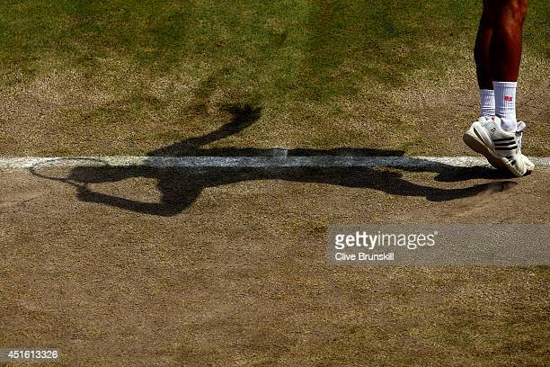 Detail shot of the shadow of Novak Djokovic of Serbia as he serves during his Gentlemen's Singles quarterfinal match against Marin Cilic of Croatia...