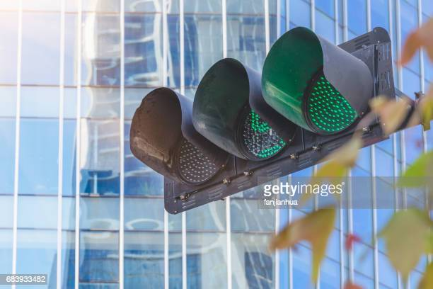 detail shot of traffic light against cityscape - semaphore stock pictures, royalty-free photos & images