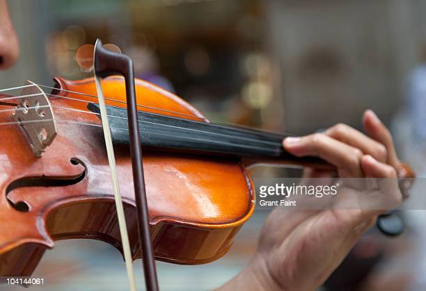 detail view man playing violin in public