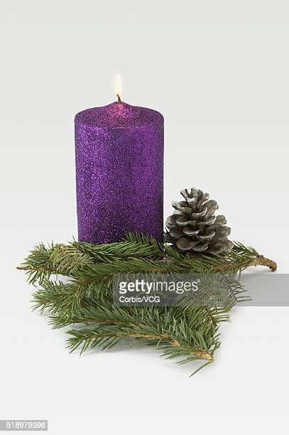 Detail view of a Christmas candle decorated with evergreen branches and a pinecone