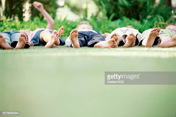 Detail view of a group of barefoot children laying on the grass