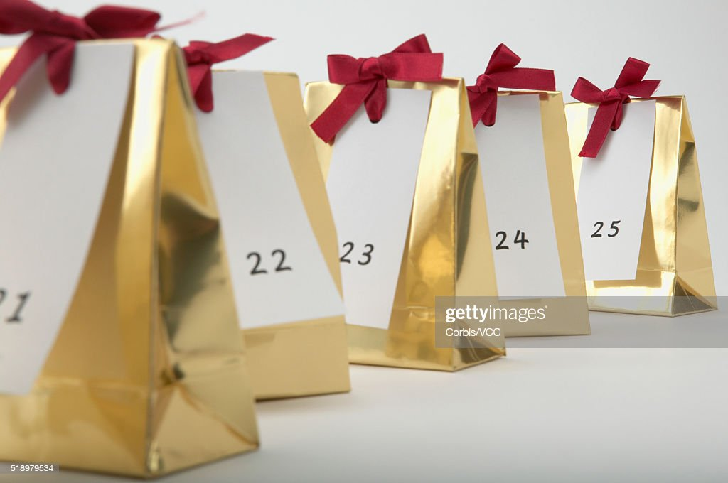 Detail view of a row of Christmas presents labeled with the numbers 21 to 25 : Stock Photo