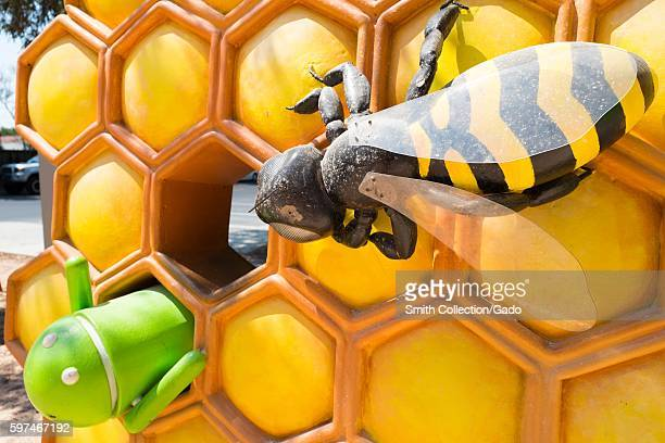 Detail view of a sculpture featuring a giant honeybee attacking a robot representing Version 30 of the Android cellphone operating system which was...