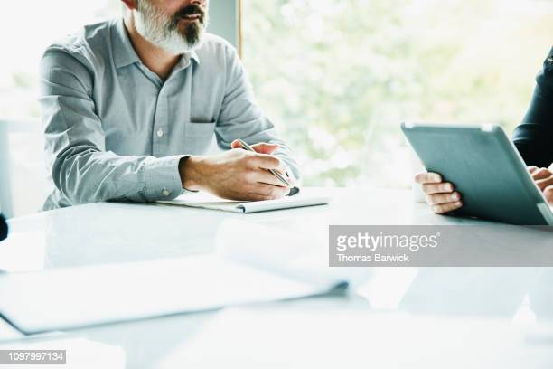 detail view of businessman holding pen during meeting in office conference room - finanzplanung stock-fotos und bilder