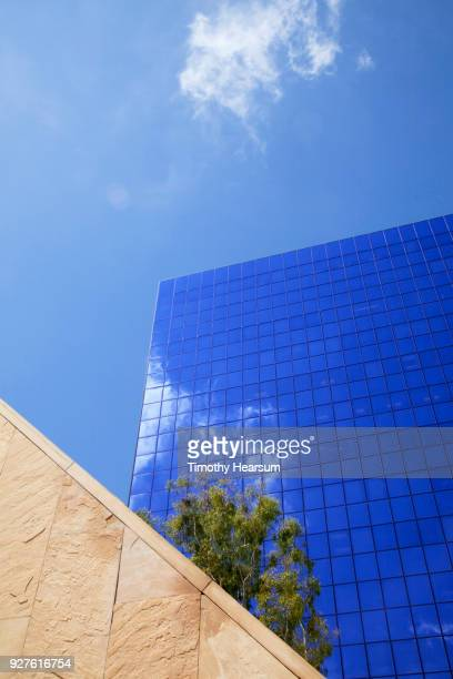 detail view of city skyscraper with cloud reflections against a mostly blue sky; neutral wall in foreground - costa mesa stock photos and pictures