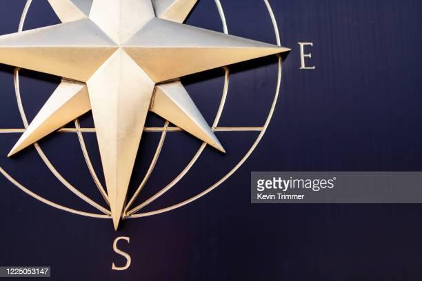 detail view of gold compass on wall - este fotografías e imágenes de stock