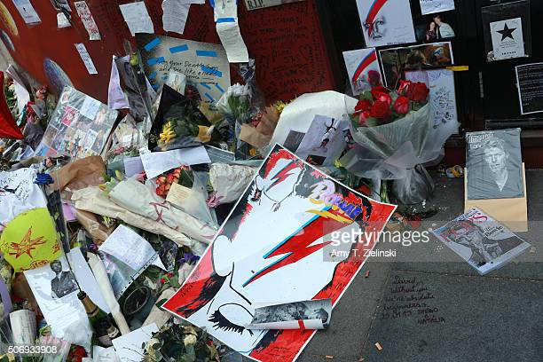 A detail view of the flowers letters and other items left on a mound continue to grow two weeks after the death of Brixton born English singer...