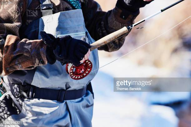 detail view of woman holding fly rod while fishing on winter morning - fingerless gloves stock pictures, royalty-free photos & images
