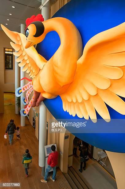 A detailed interior view shows a large sculpture of Tezuka Osamu's manga character, 'Hi no Tori' Phoenix