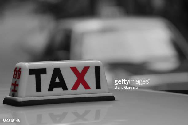 Detailed shot of taxi sign reflected on car roof and against blurred traffic