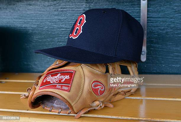 A detailed view of a Boston Red Sox baseball hat and Rawlings glove sitting in the dugout prior to the game against the Detroit Tigers at Comerica...