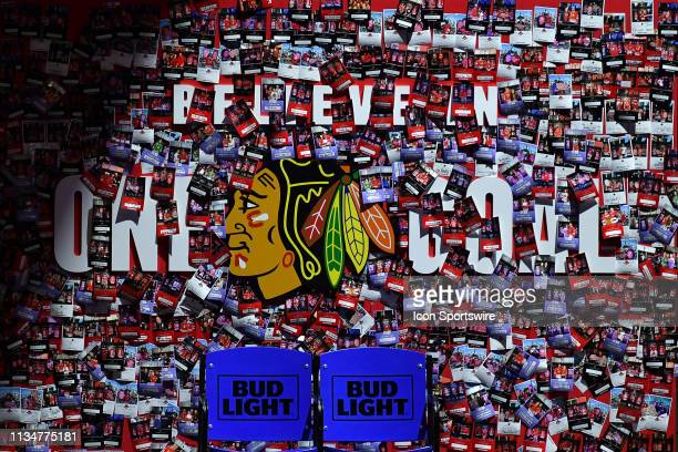 A detailed view of a Chicago Blackhawks fan zone picture wall with the Chicago Blackhawks logo and the Believe in One Goal mantra is seen in first...