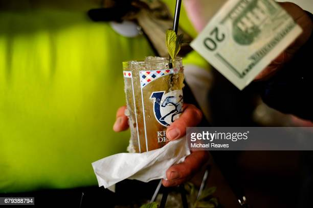 A detailed view of a race fane holding a Mint Julep and a 20 dollar bill prior to the 143rd running of the Kentucky Oaks at Churchill Downs on May 5...