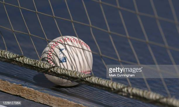 A detailed view of a Rawlings official Major League Baseball sitting on top of the dugout behind the protective netting during the game between the...
