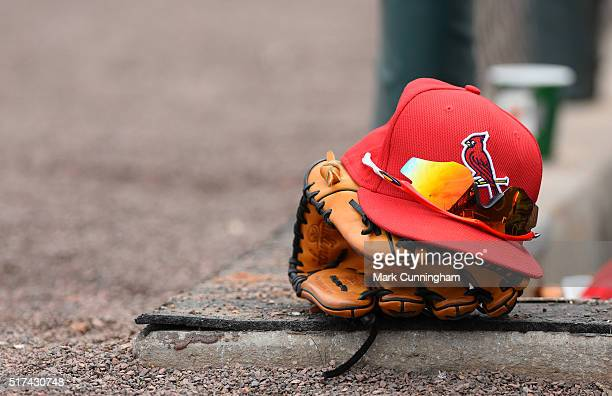 A detailed view of a St Louis Cardinals hat glove and sunglasses sitting in the dugout during the Spring Training game against the Detroit Tigers at...