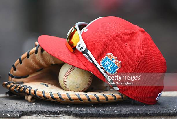 A detailed view of a St Louis Cardinals hat glove baseball and Under Armour sunglasses sitting in the dugout during the Spring Training game against...