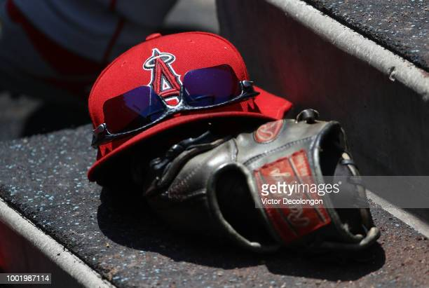 A detailed view of an Los Angeles Angels of Anaheim hat and a catching glove is seen during the second inning of the MLB game between the Los Angeles...
