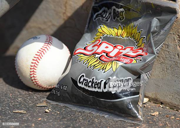 A detailed view of an official baseball and a bag of Spitz sunflower seeds sitting in the dugout during the game between the Minnesota Twins and the...