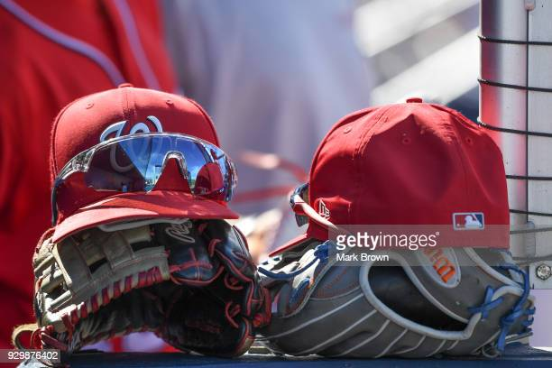 A detailed view of ballcaps gloves and sunglasses of the Washington Nationals in the dugout during the spring training game at FITTEAM Ballpark of...