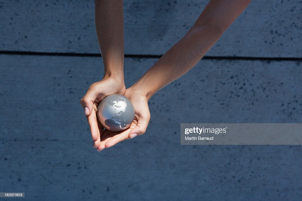 Detailed View of hands holding globe outdoors : Stock Photo