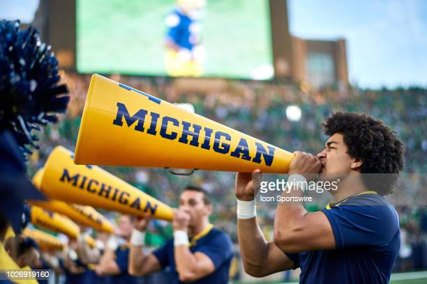 A detailed view of Michigan Wolverines cheerleaders using the Michigan Wolverines megaphones is seen in game action during the college football game...