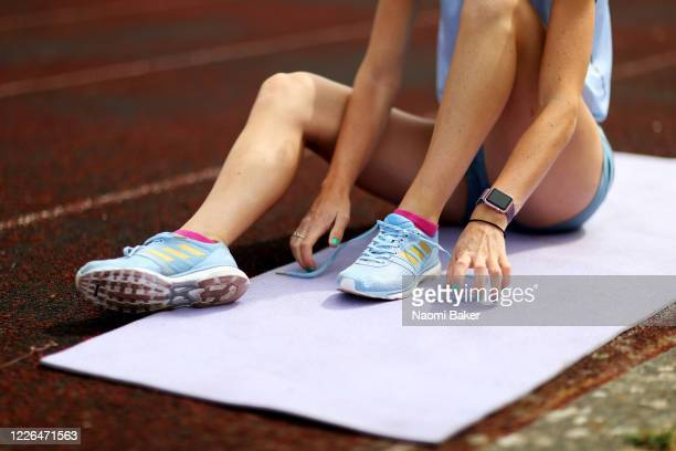 A detailed view of Paralympian Olivia Breen of Great Britain tying up her shoe laces as she continues to train in isolation at a local running track...