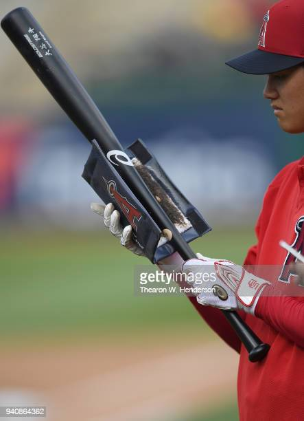 A detailed view of Shohei Ohtani of the Los Angeles Angels of Anaheim rubbing pine tar on his Asics bat during batting practice prior to the start of...
