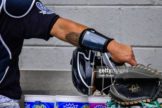 A detailed view of the armband with the name Tanaka on it worn by Gary Sanchez of the New York Yankees while warming up in the bullpen prior to the...