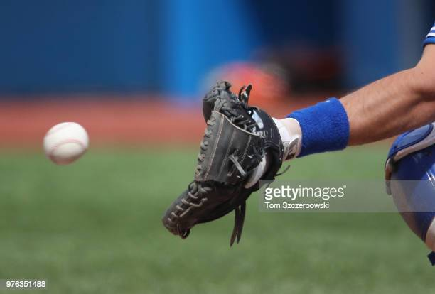 A detailed view of the glove worn by Luke Maile of the Toronto Blue Jays as he handles a pitch while crouching behind home plate during MLB game...