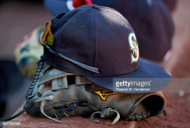 A detailed view of the hat and Mizuno baseball glove belonging to Ben Gamel of the Seattle Mariners sitting on the dugout steps against the Oakland...